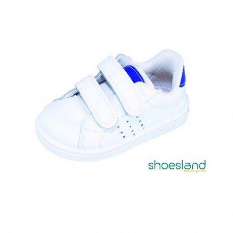 37974e0cabeac Zapatillas deportivas para niños tipo tenis de piel color blanco con  detalle en azul cerradas con