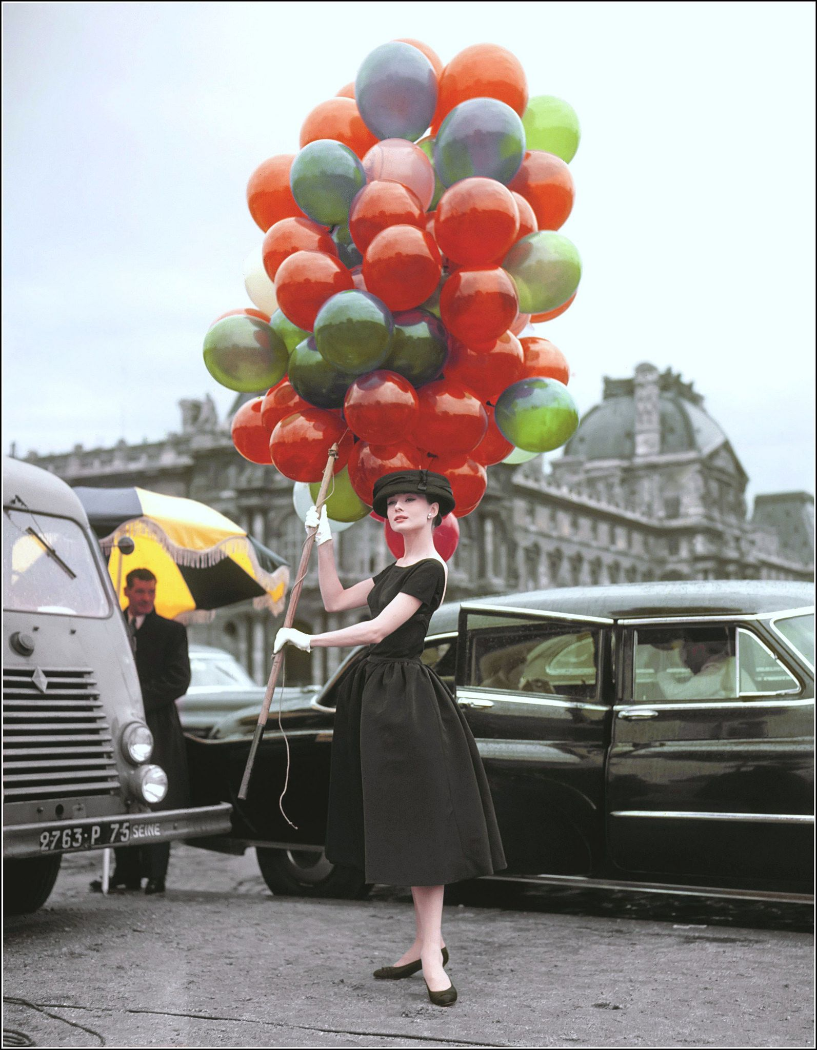 """Audrey Hepburn in dress by Givenchy poses on location in Paris during the filming of """"Funny Face"""", 1956"""