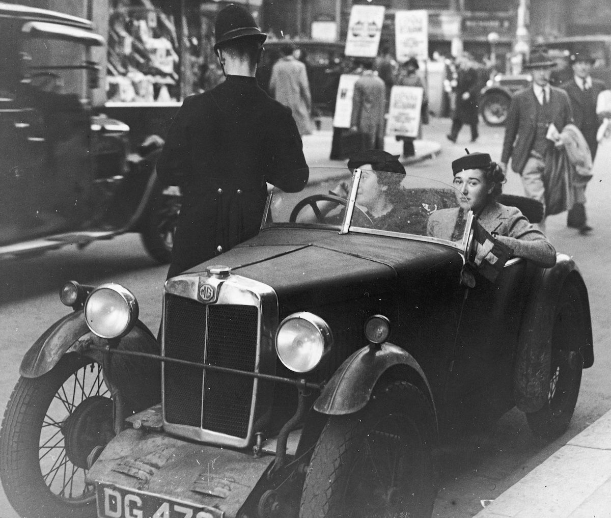 London motorists in an MG M-type receive a ticket from a traffic policeman on the corner of Wardour Street.