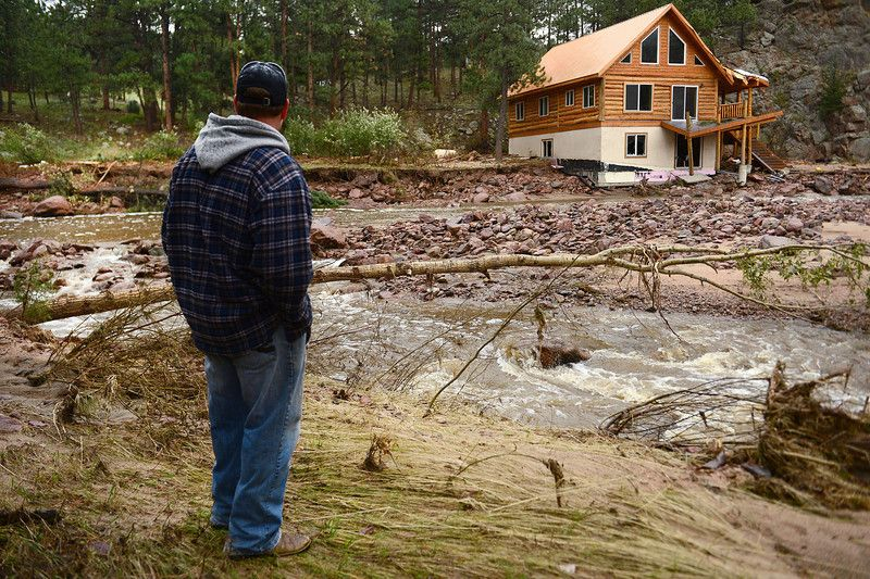 Pinewood Springs resident Judd Payne looks at the damage to his neighborhood which has rendered their community an island.  Kiowa Road is co...