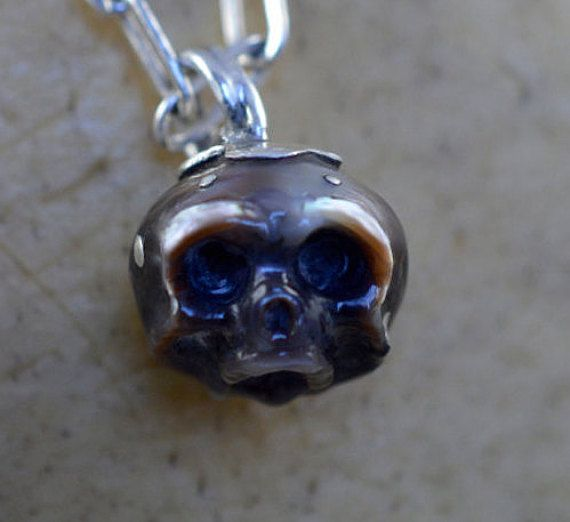 Dark pearl hand carved into a skull by Arlo. Multicolored, hues of black/brown/grey. Sterling silver spots through out the skull. Sterling silver