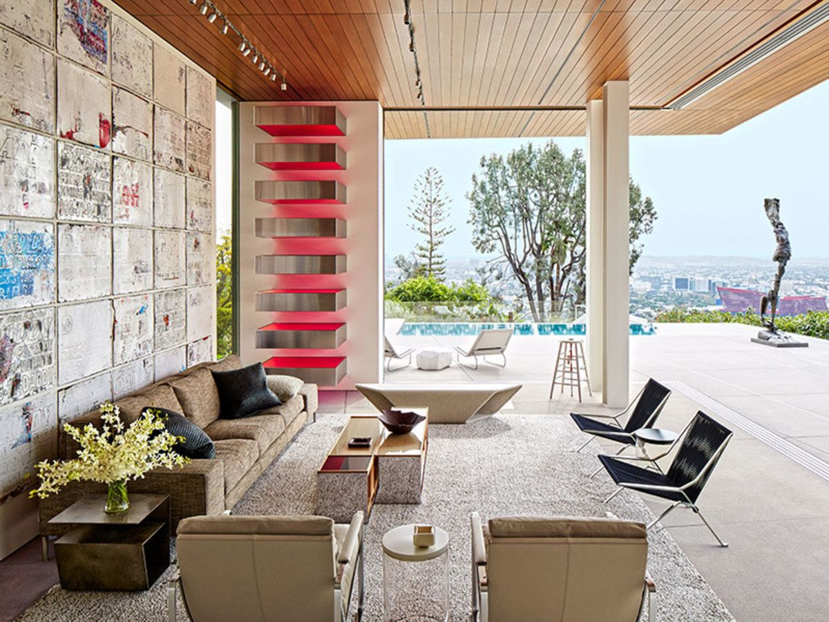 The architecture firm McRitchie Design collaborated with Gary Hutton Design on the renovation of collector Chara Schreyer's gallery-like Los Angeles home, which has expansive views of the city. In the family room, a multipanel collage work by Mark Bradford and one of Donald Judd's Stack sculptures overlook a sofa designed by Piero Lissoni for Living Divani, an angular Council bench, a pair of Poul Kjærholm steel-and-rope chairs by Fritz Hansen, and a B&B Italia cocktail table; the carpet...