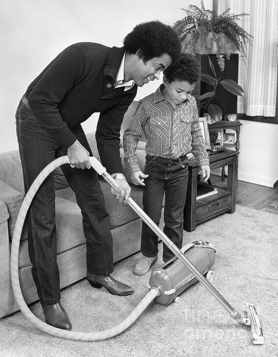 African American Father And Son Vacuuming The Living Room Carpet