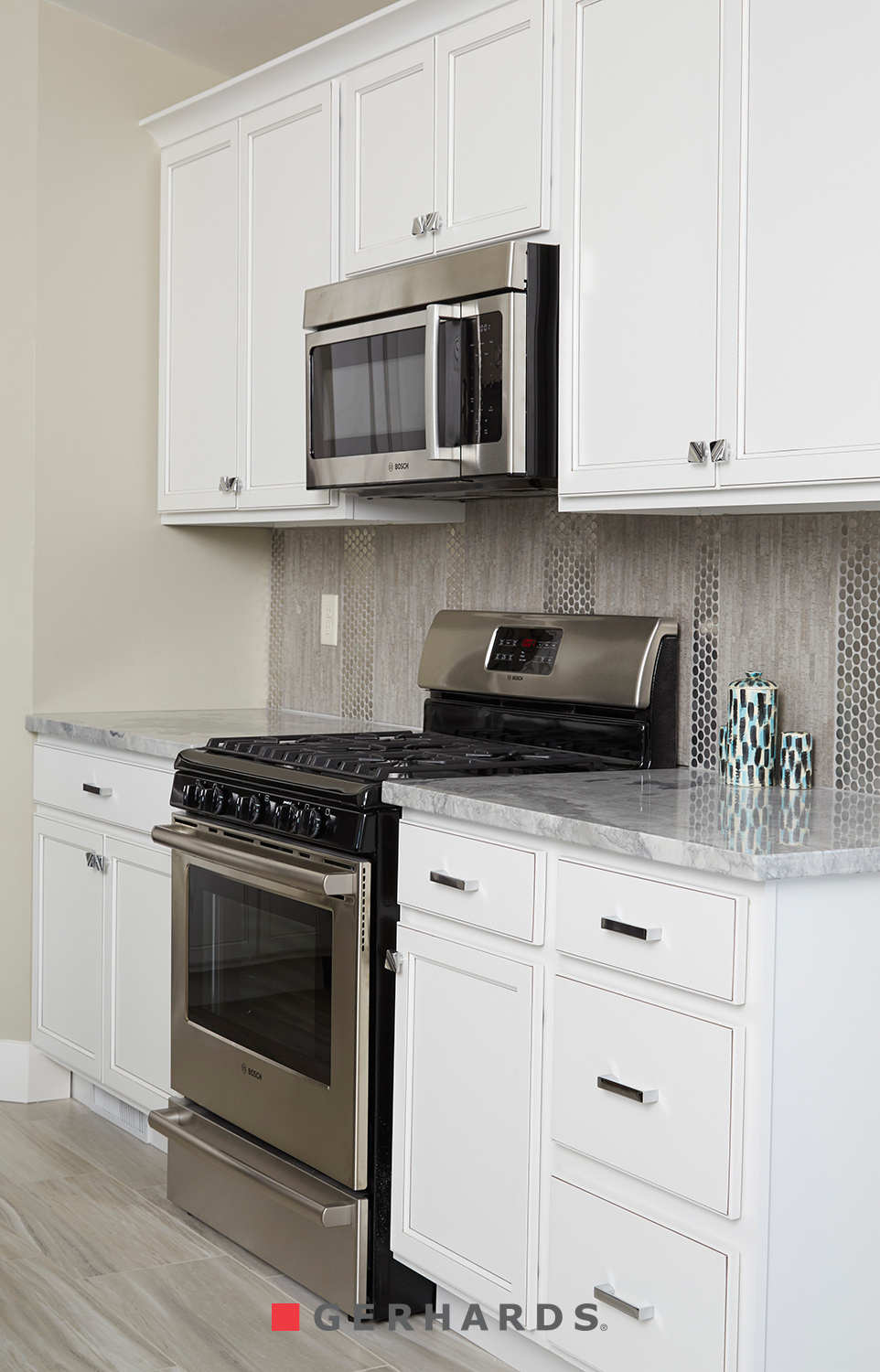 Shiny Backsplash In A Vertical Pattern White Cabinetry By