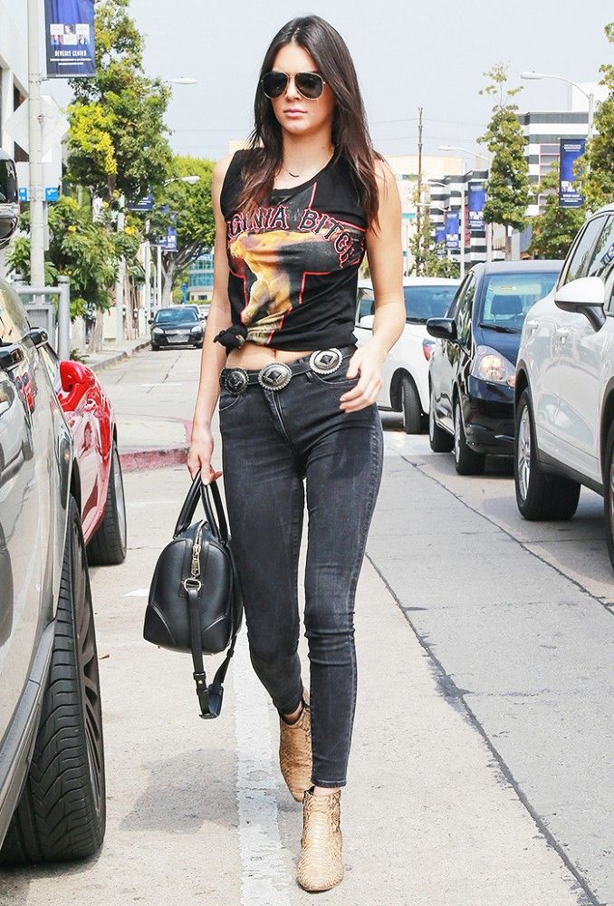 Kendall Jenner wears a graphic tee, black skinny jeans, python printed ankle boots and a black structured bag.
