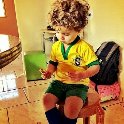 Cute little boy with beautiful curly hair in his soccer uniform