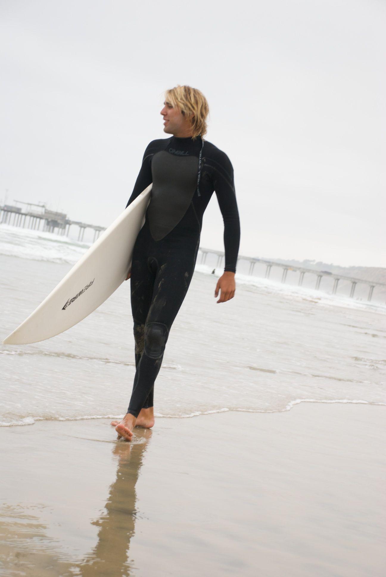 California surfer walking along the beach near La Jolla