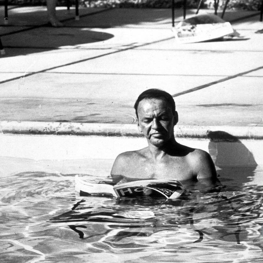 Frank Sinatra reading in the pool at his Palm Springs home.
