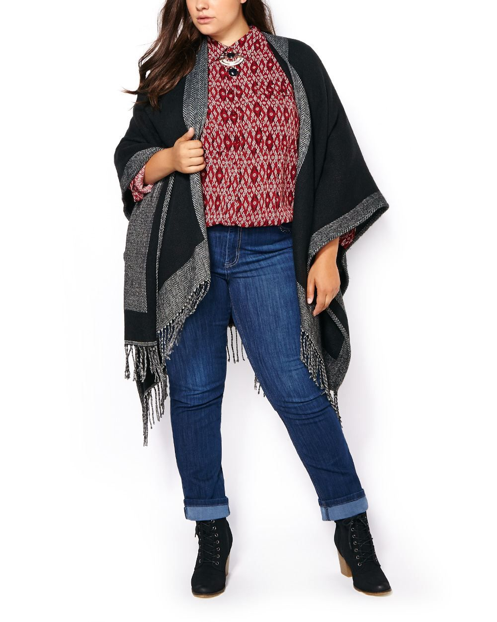 """Cover up for fall with this gorgeous plus-size cape! Made with a cozy knit fabric, it has a contrasting trim with chevron pattern, fringe hem and trendy cape design. A coveted top layer for cold days ahead! Length: 59"""", Width: 54"""""""