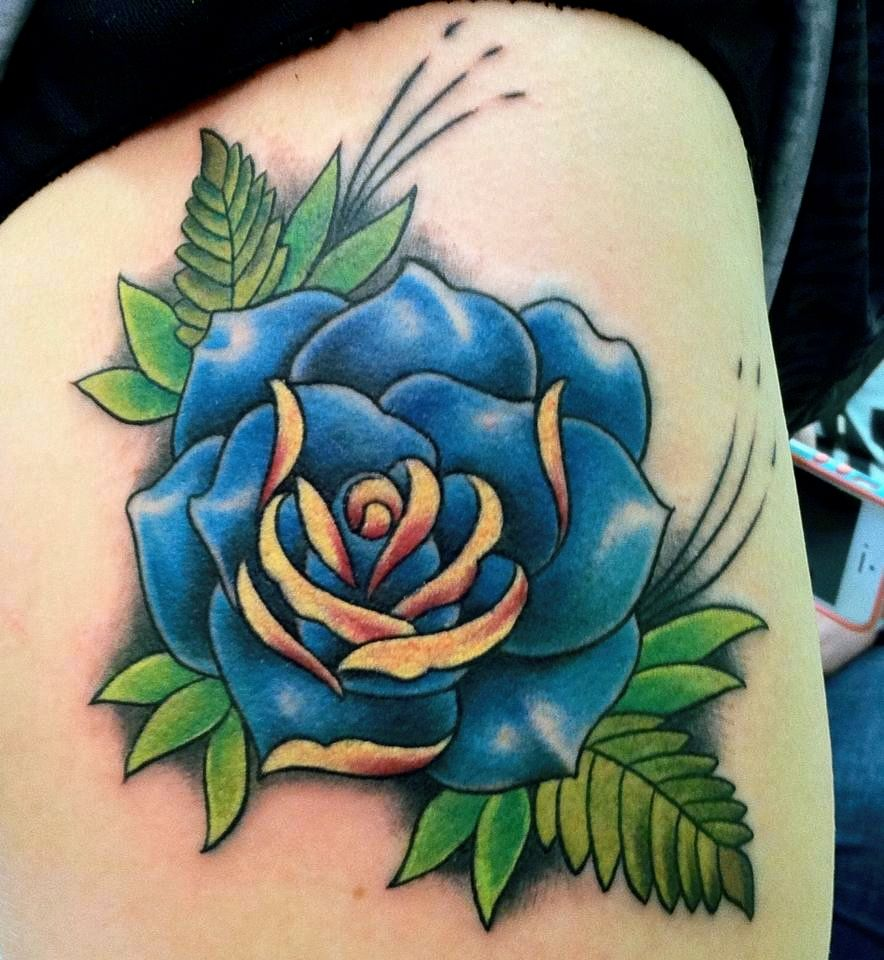 Traditional blue rose tattoo on thigh