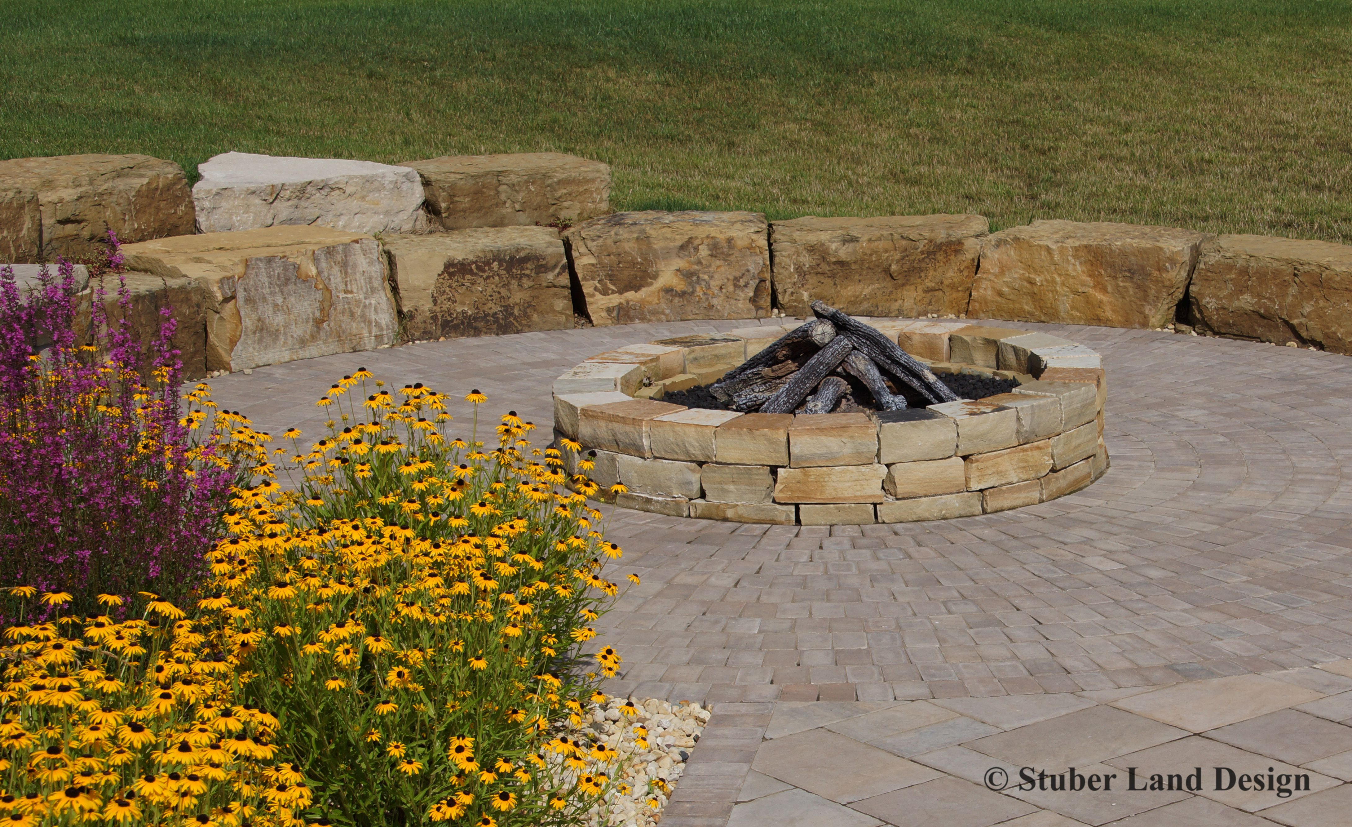 Large Chunks Of Natural Stone Outcropping Create A Retaining Wall And Double As Seating For This Fire Pit Wall Seating Landscape Walls Retaining Wall