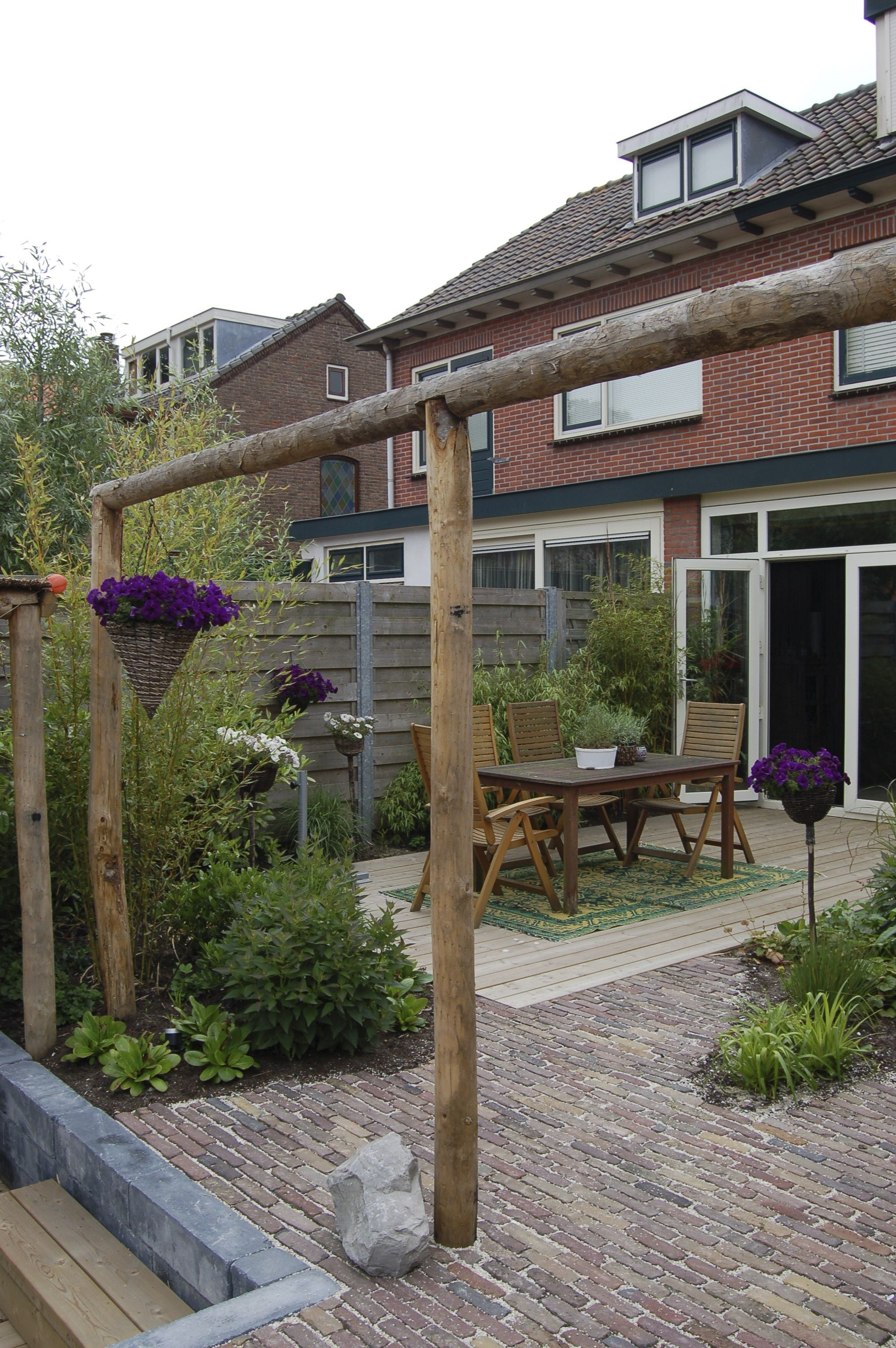 Achtertuin met overdekte zitkuil wintergroene beplanting en pergola van kastanjehout www - Overdekte patio pergola ...