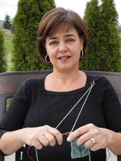 Andrea Wong shows the basic setup for doing Portuguese knitting, tensioning the yarn through a pin on her left shoulder, on the Knitting Daily blog. [More knitting tech at https://www.pinterest.com/yrauntruth/fiber-knit-techniques-tutorials/ ]