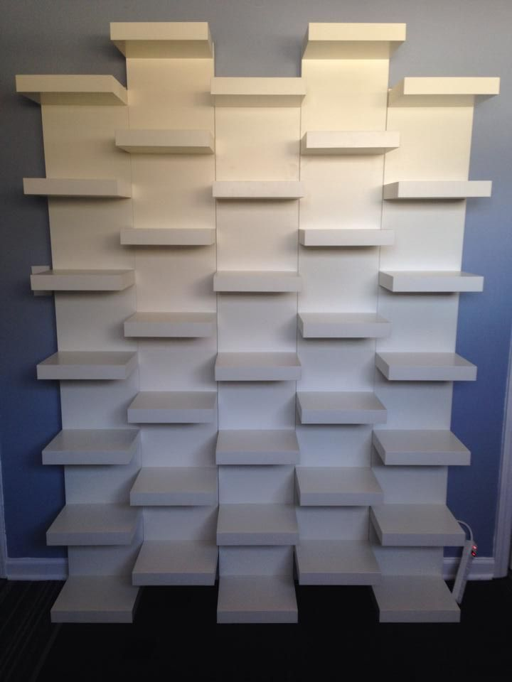 Such a simple way to get a very unique and striking bookshelf design. - Ikea Lack book shelves mounted together in a staggered pattern to create built in bookends for the other shelves!