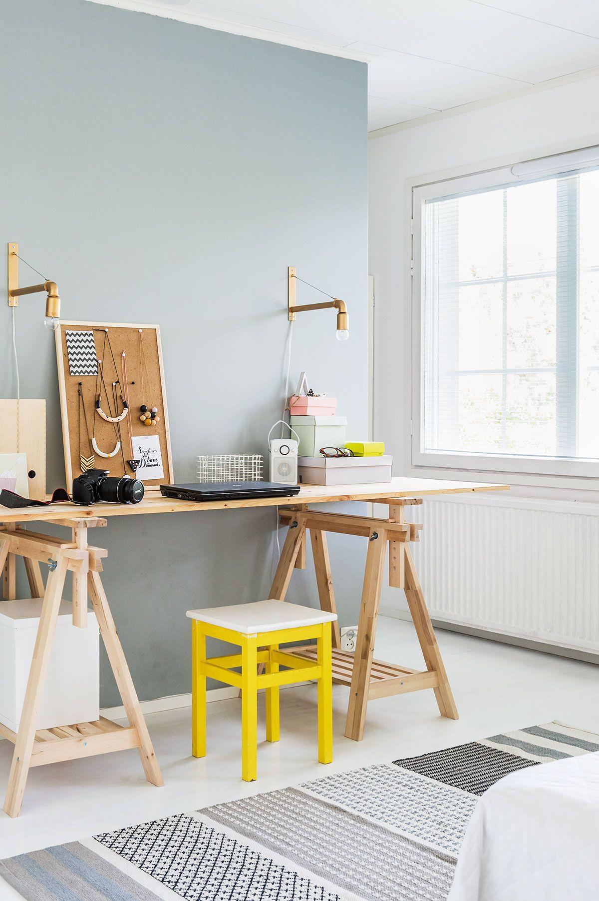 Makuuhuoneen työpisteen pöytä tehtiin liimapuu-levystä ja Ikean pukkijaloista. Korkkitaulussa roikkuvat korut Rilla on tehnyt Fimo-massasta. Matto on Vallilan. Harmaaksi maalatun seinän takana on vaatehuone, jonne pääsee kulkemaan työpisteen molemmilta puolilta.