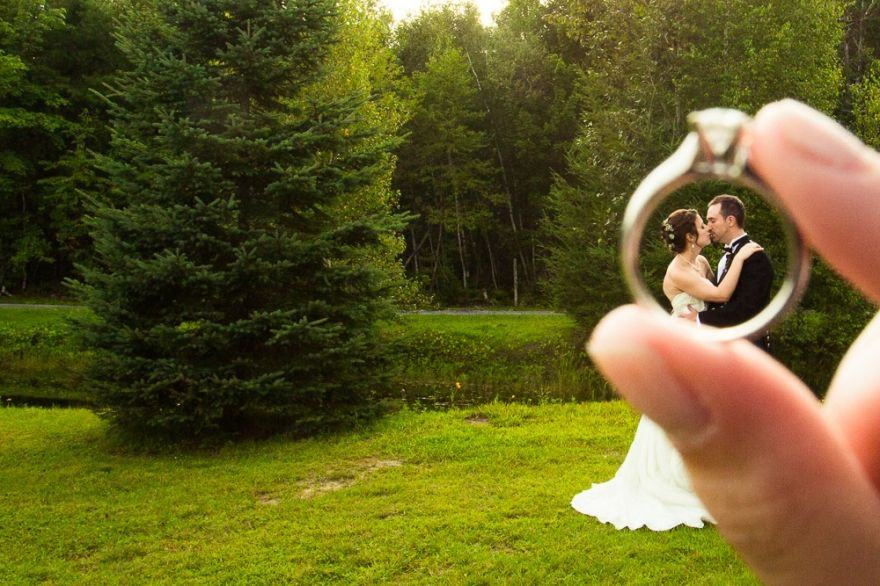 Married couple framed by their engagement ring in a creative wedding photo.by Ottawa wedding photographers, Kandid Weddings.