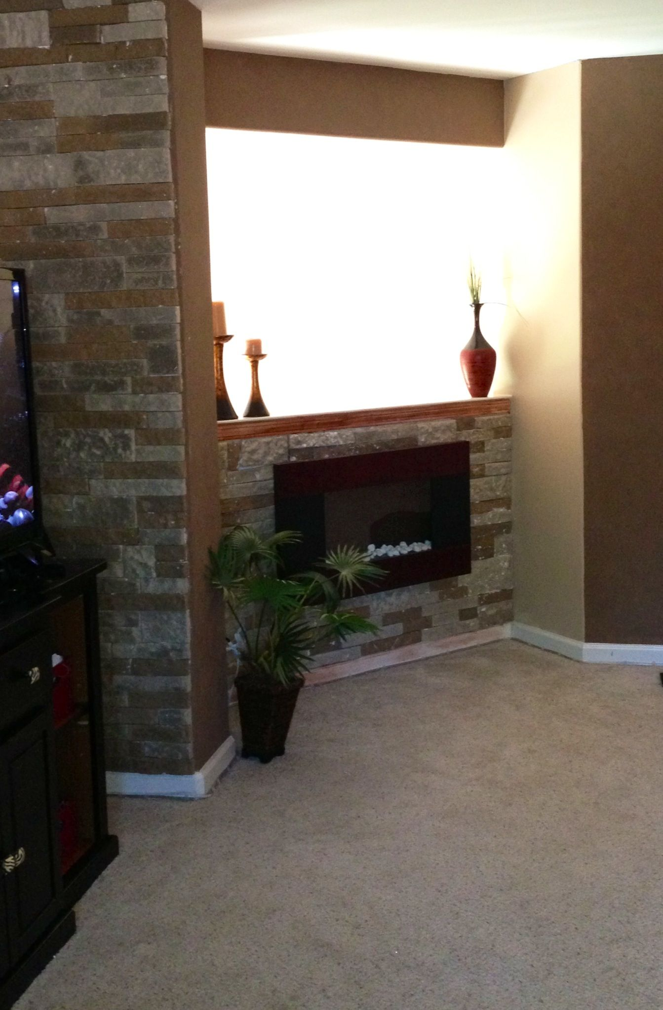 Electric fireplace surrounded by airstone lowe 39 s diy for Fireplace half stone