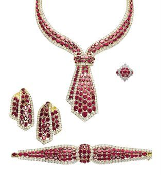 A SUITE OF RUBY AND DIAMOND JEWELLERY   The necklace of tie design, set with lines of oval-shaped rubies bordered by brilliant-cut diamonds, a bracelet, a pair of ear clips and a ring en suite, mounted in gold, the ring mounted in platinum and gold, necklace 39.0 cm, bracelet 17.5 cm, ear clips 6.0 cm, ring size 6 (4)