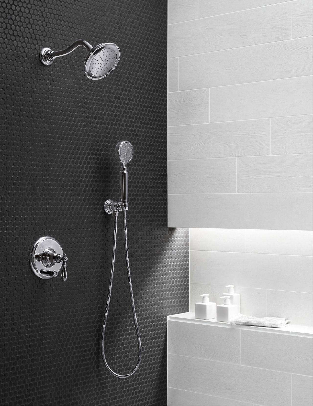 Black tile meets white marble with chrome Kohler Artifacts shower