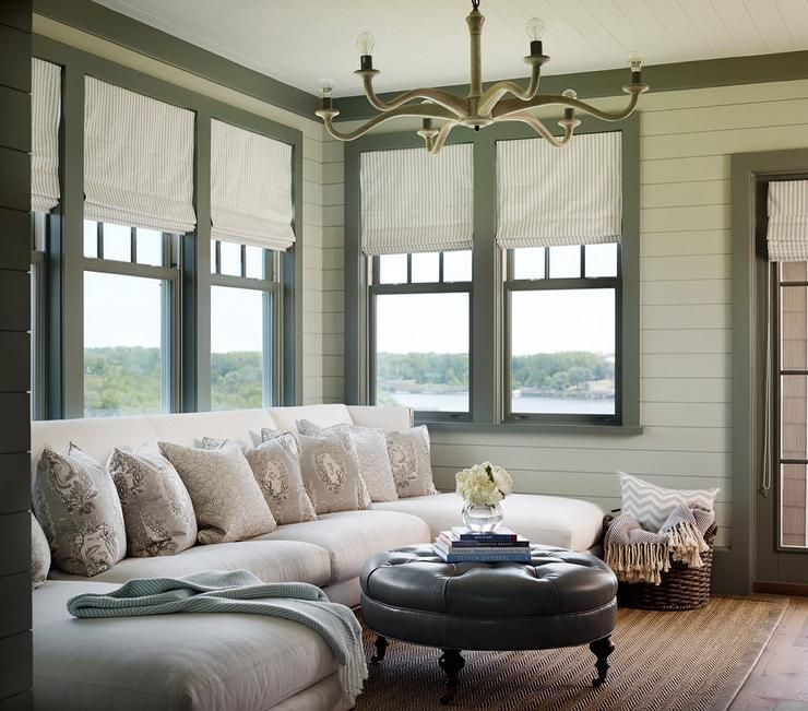 White and green living room features walls clad in white shiplap finished with green moldings framing windows dressed in gray pinstripe roman shades placed over a white sectional fitted with two chaise lounges facing a round black leather tufted ottoman on caster legs doubling as a coffee table atop a bound herringbone jute rug.
