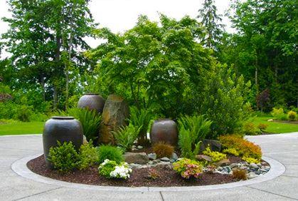 island bed incorporating big pots rocks and plants