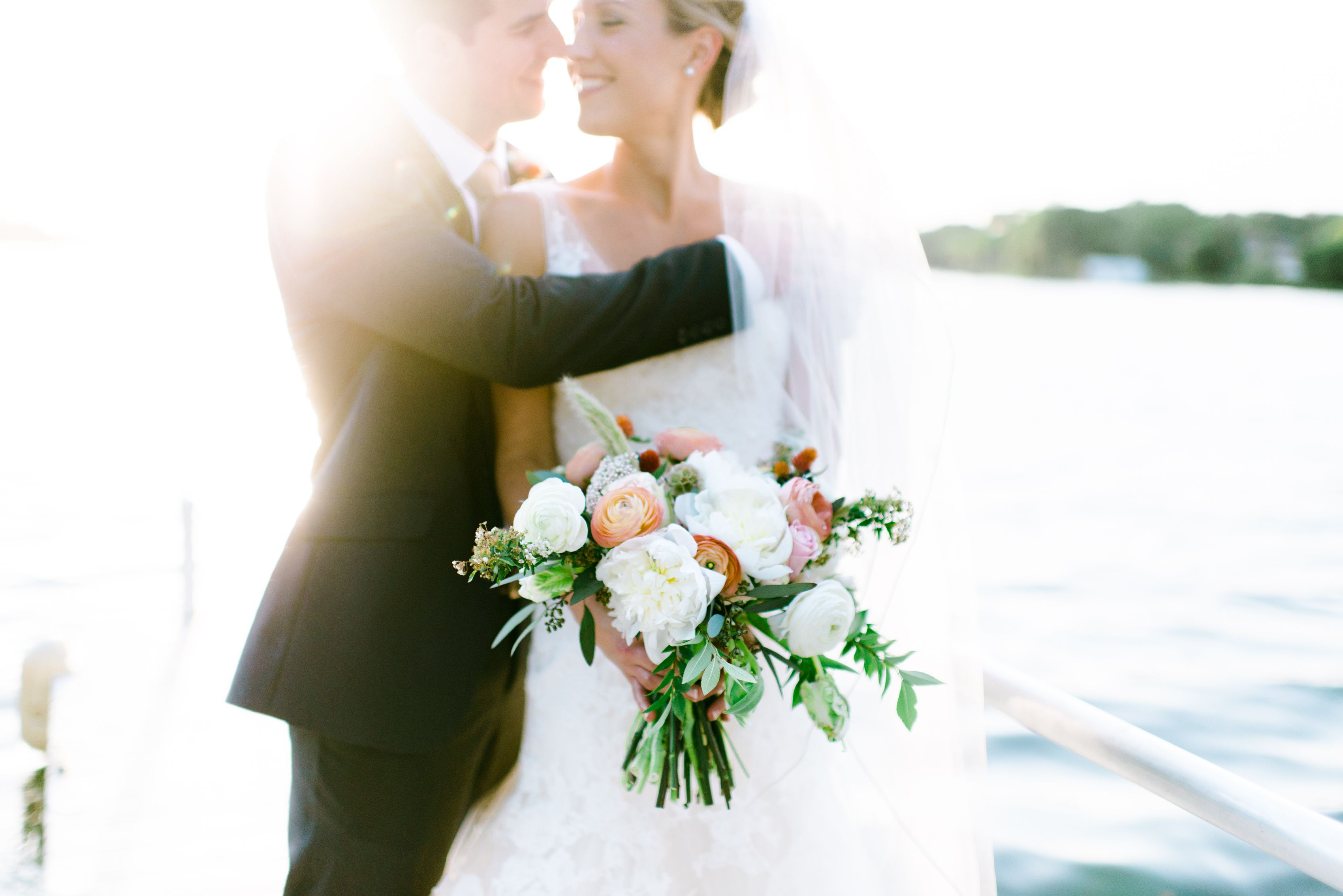 the bride and groom share a moment at their lakeside reception. she holds her loose bridal bouquet of white peony, peach roses, white ranunculus, rosita vendela roses, white majolik spray roses, bunny tail grass, pink rice flower, peach ranunculus, scabiosa pods, white spirea, white parrot tulips, elm & seeded eucalyptus
