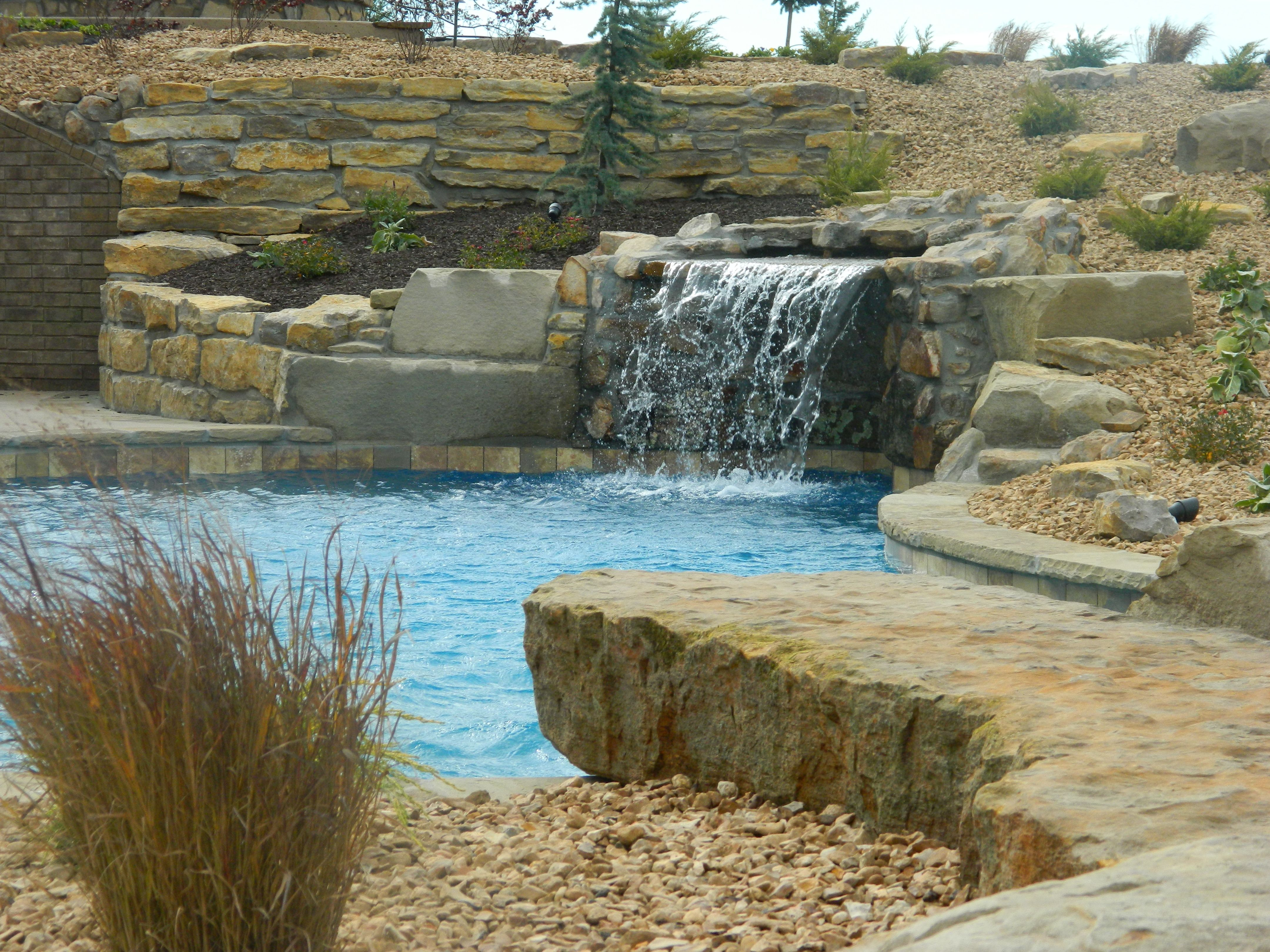Blue haven pools kc grotto waterfall built into hillside for Building a pool