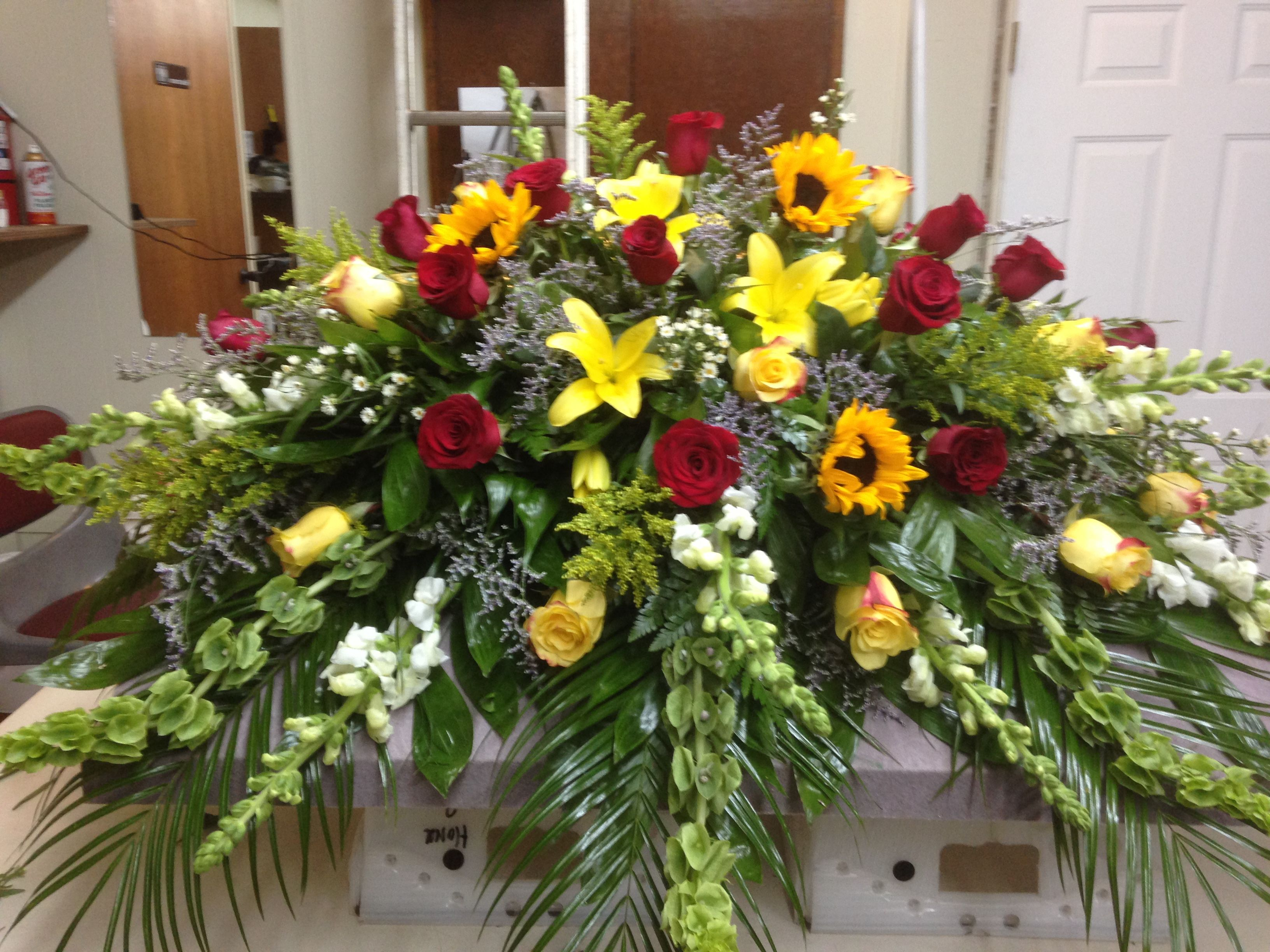 Casket spray using yellow lilies yellow roses red roses casket spray using yellow lilies yellow roses red roses sunflowers bells of izmirmasajfo