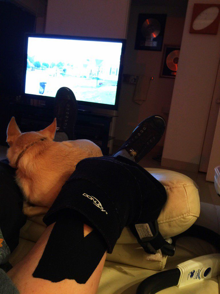 Daddy icing his knee. ToTo sleeping on the other knee... I love our furs.