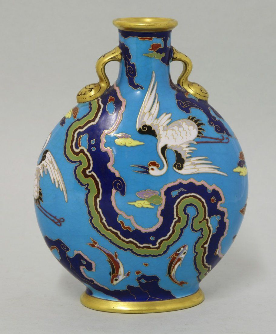 A Minton pilgrim flask, attributed to Dr Christopher Dresser, c.1870, of compressed circular form with a short neck, with gilt lug handles, the bleu celeste ground decorated with cranes, scrolling clouds and leaping carp, impressed 1348, 20cm high