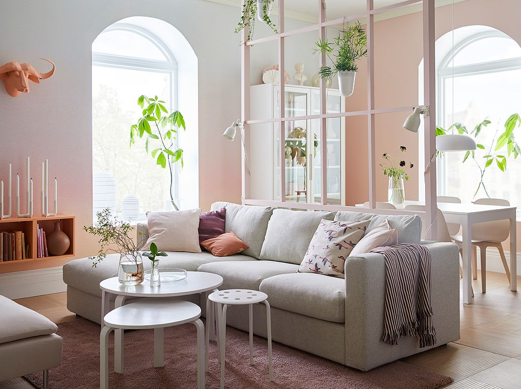 A pink and white living room with beige sofa with chaise longues and ...