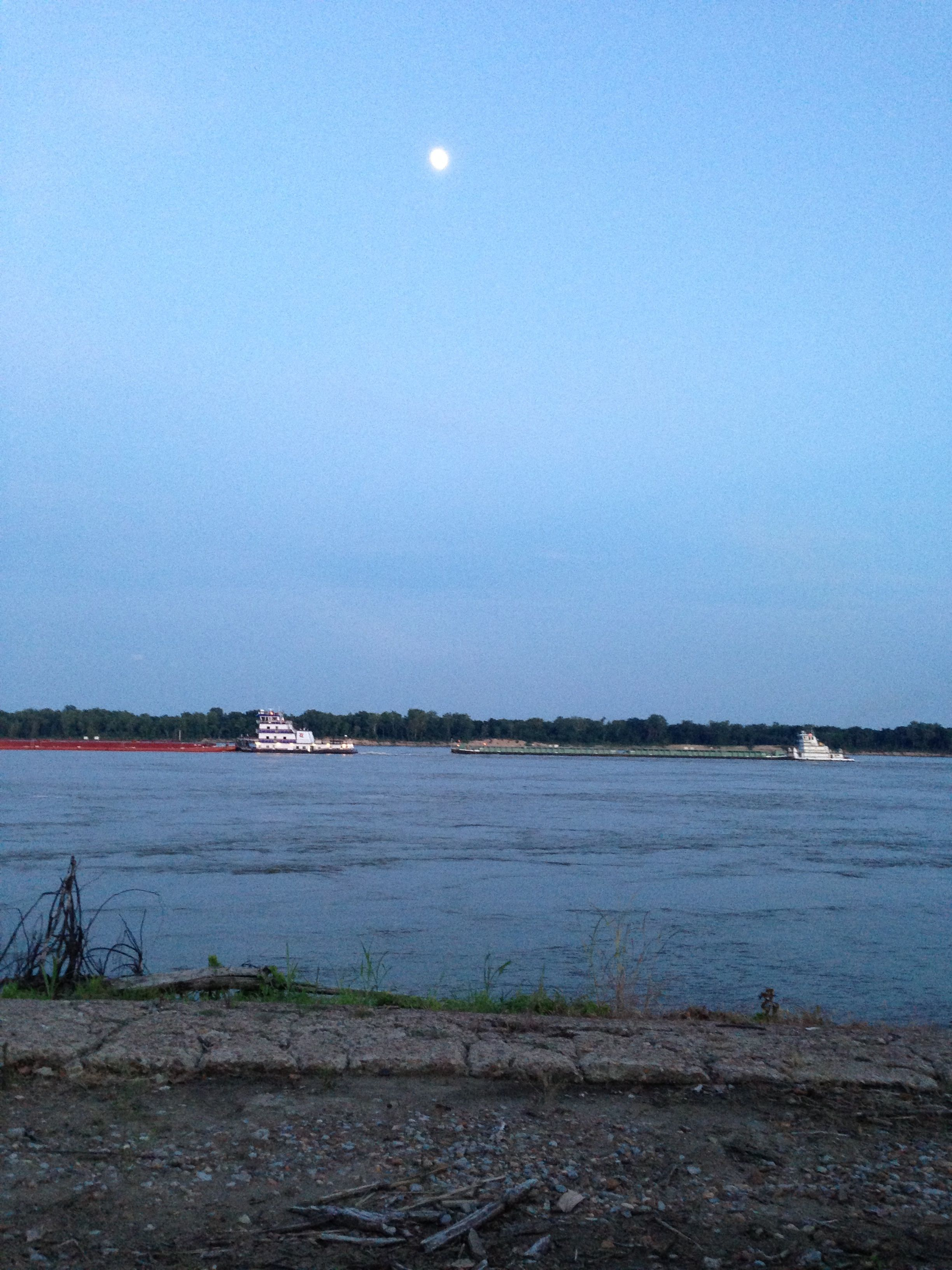 Sun setting, moon rising, tug boats moving cargo north on the Mississippi.