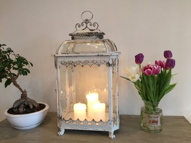 A white metal lantern that has a distressed paint finish