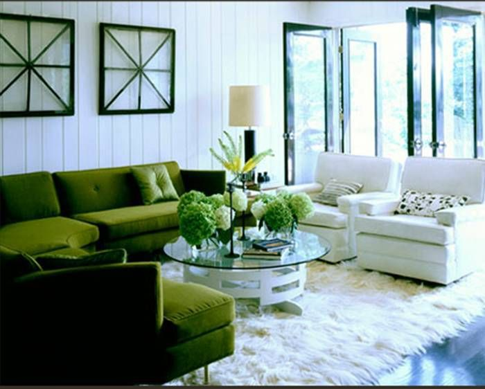 Living room with a green velvet sectional sofa, white beadboard walls, two white…