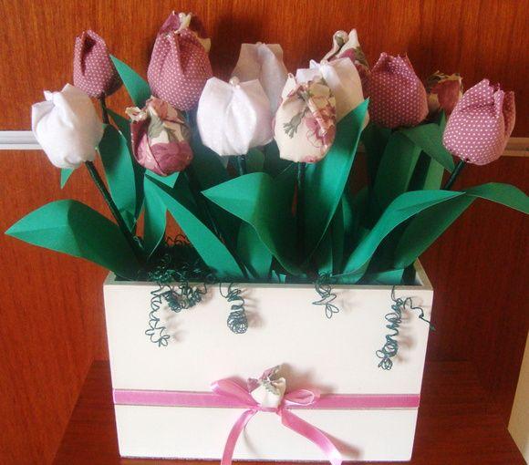 Vaso em MDF pintura branca;  Tulipas de tecidos diversos com cabo de madeira, folhas de papel e detalhe com perolas e fitas de cetim.  Design bem elaborado com detalhes e boa estruturação das cores.  O valor do trabalho depende da quantidade de tulipas e tamanho do vaso.  Na foto, o cachepô de madeira contém 13 tulipas; medidas: 25 x 7 x 15 cm. Valor estimado de R$ 95,00.  Envie-nos um email e obtenha mais informações.