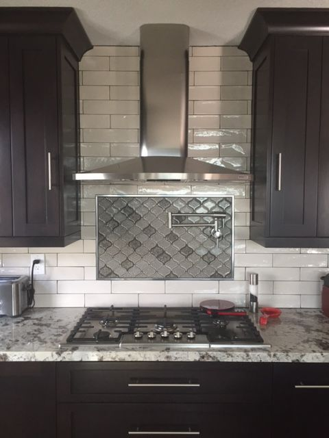 Kitchen backsplash design with handcrafted glossy white subway tile and decorative glass mosaic above stove cooktop also