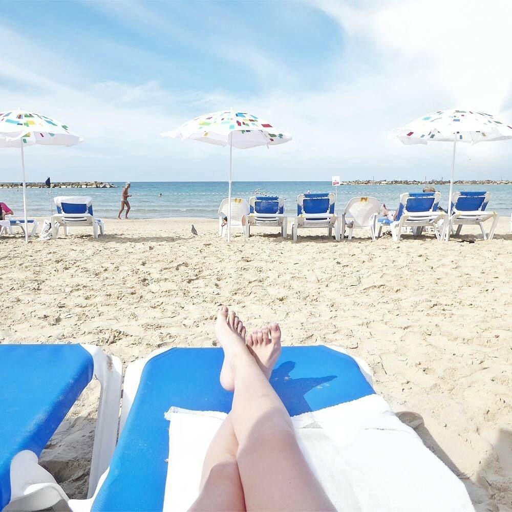 Lounging On Beach In Tel Aviv Israel With Blue Sun Umbrellas Looking At The Water Mediterranean Sea Tel Aviv Israel Beach Travel