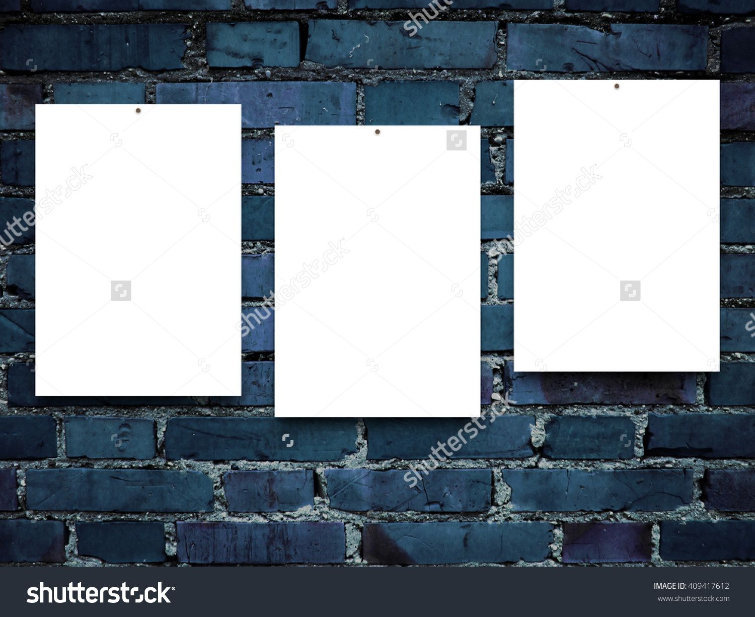 Close-up of three nailed blank frames on blue brick wall background