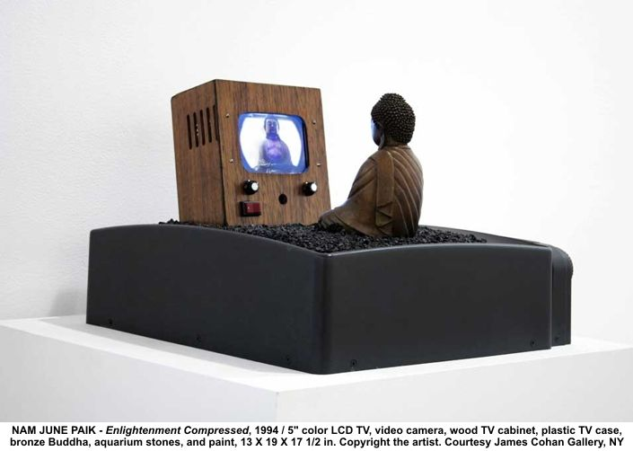 "Nam June Paik, ""Enlightenment Compressed"", (TV Buddha), (1994)  -  5"" color LCD TV, video camera, wood TV cabinet, plastic Tv case, Bronze Buddha, aquarium stones and paint, 13x19x17 inc./Copyright of Artist, NYC."