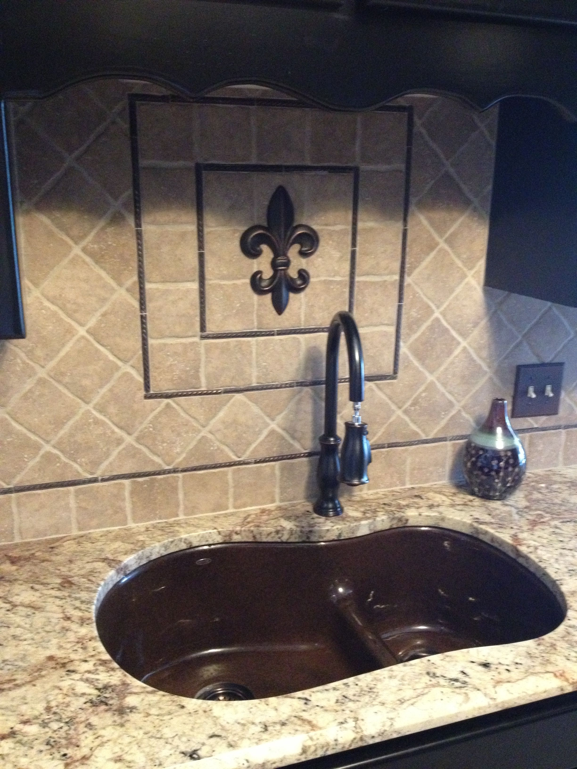 Fleur de lis backsplash i got the fdl from hobby lobby and painted it to match the bronze pieces from lowes that i was using for my backsplash