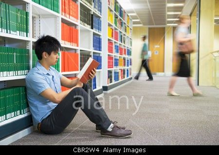 Chinese Man Reading Book In Library C Blend Images Alamy