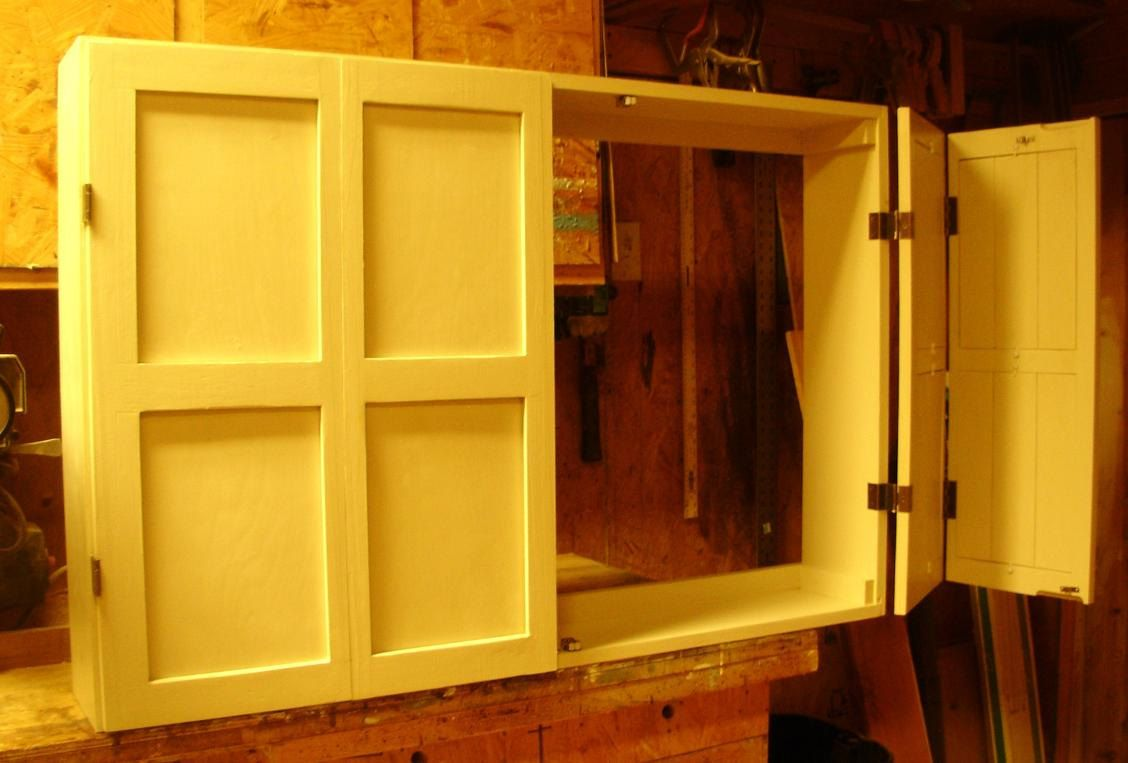 Bi fold doors on a large cabinet tv cover wall by for Bi fold doors for kitchen cabinets