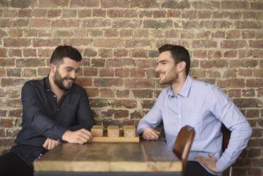 """Mannequin Hommes Photo Lifestyle Chemises Hanjo - Bar à vin le JaJa (Lille) - Hommes à table en train de jouer - Chemise """"La Tourbée"""" (Brut / 79€) et chemise à fines rayures """"La Canaille"""" (79€)"""