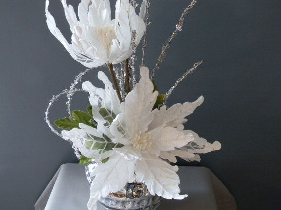 Reserved listing for Terece:  This elegant winter centerpiece consists of white velvet fantasy poinsettia blooms with silver sparkle stems in a beautiful mercury glass container. This arrangement is absolutely stunning and adds an elegance to your winter decor. The height is about 30 and the width is about 12-13
