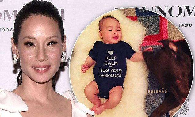 Lucy Liu's baby Rockwell pets the family Labrador Apple