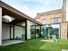 Een nieuwe glazen l vormige uitbreiding op een bestaande woning