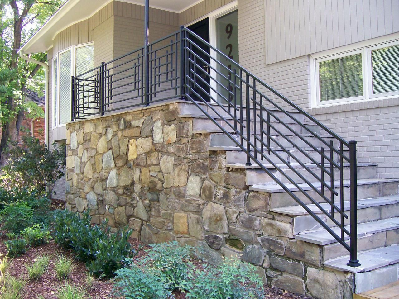 Outdoor stone steps and iron railing hgtv front steps for Exterior balcony railing design