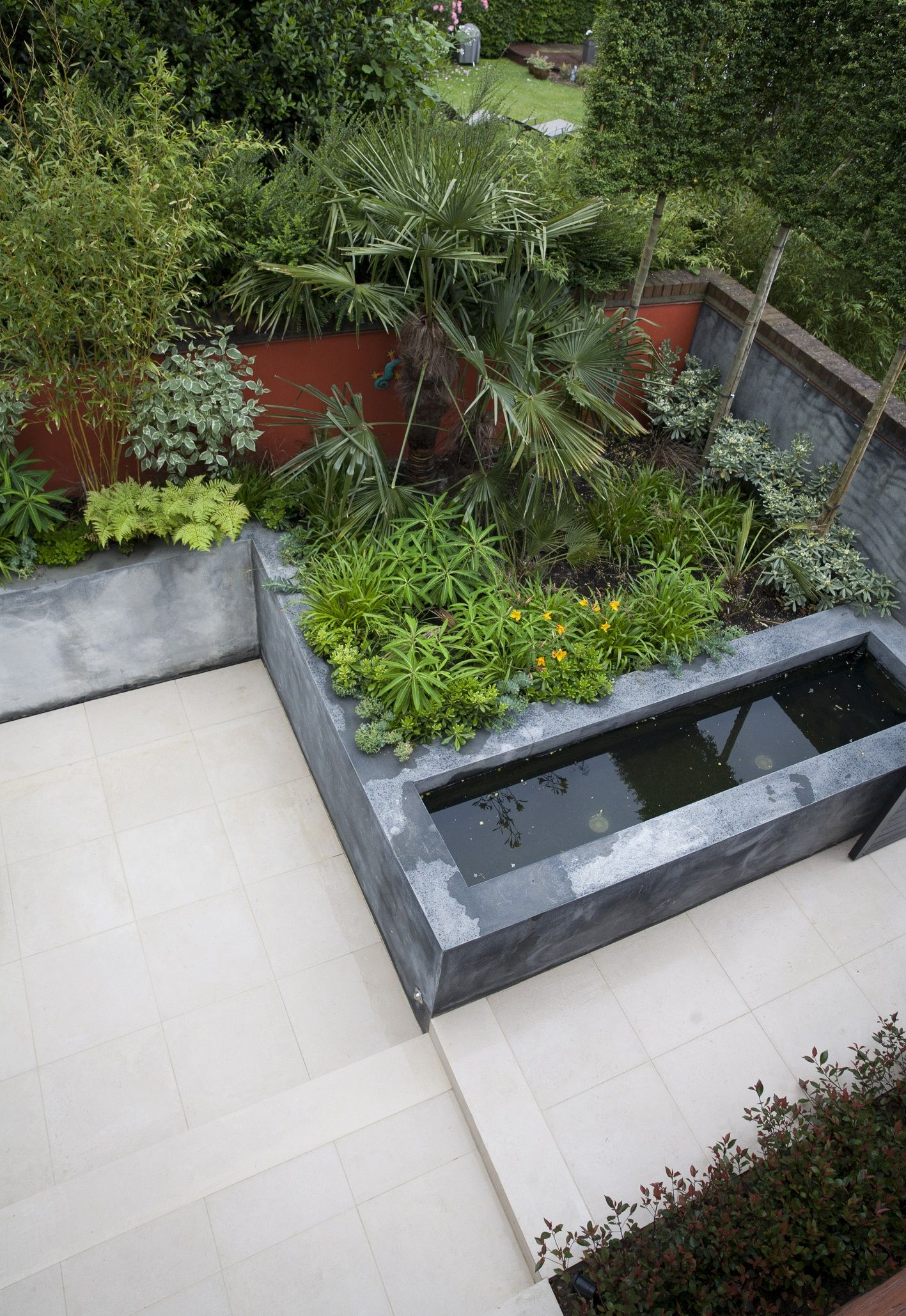 A view down onto the courtyard. From right to left the garden steps down to provide more secrecy and seclusion. The water feature lights up at night and the limestone  flooring is washed with a soft glow.