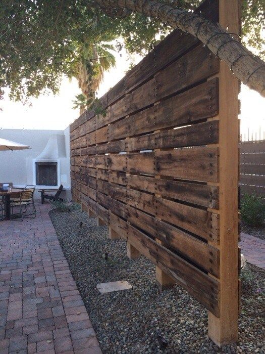 Reclaimed barn wood panels to create a horiztonal privacy fence for the hot  tub, the