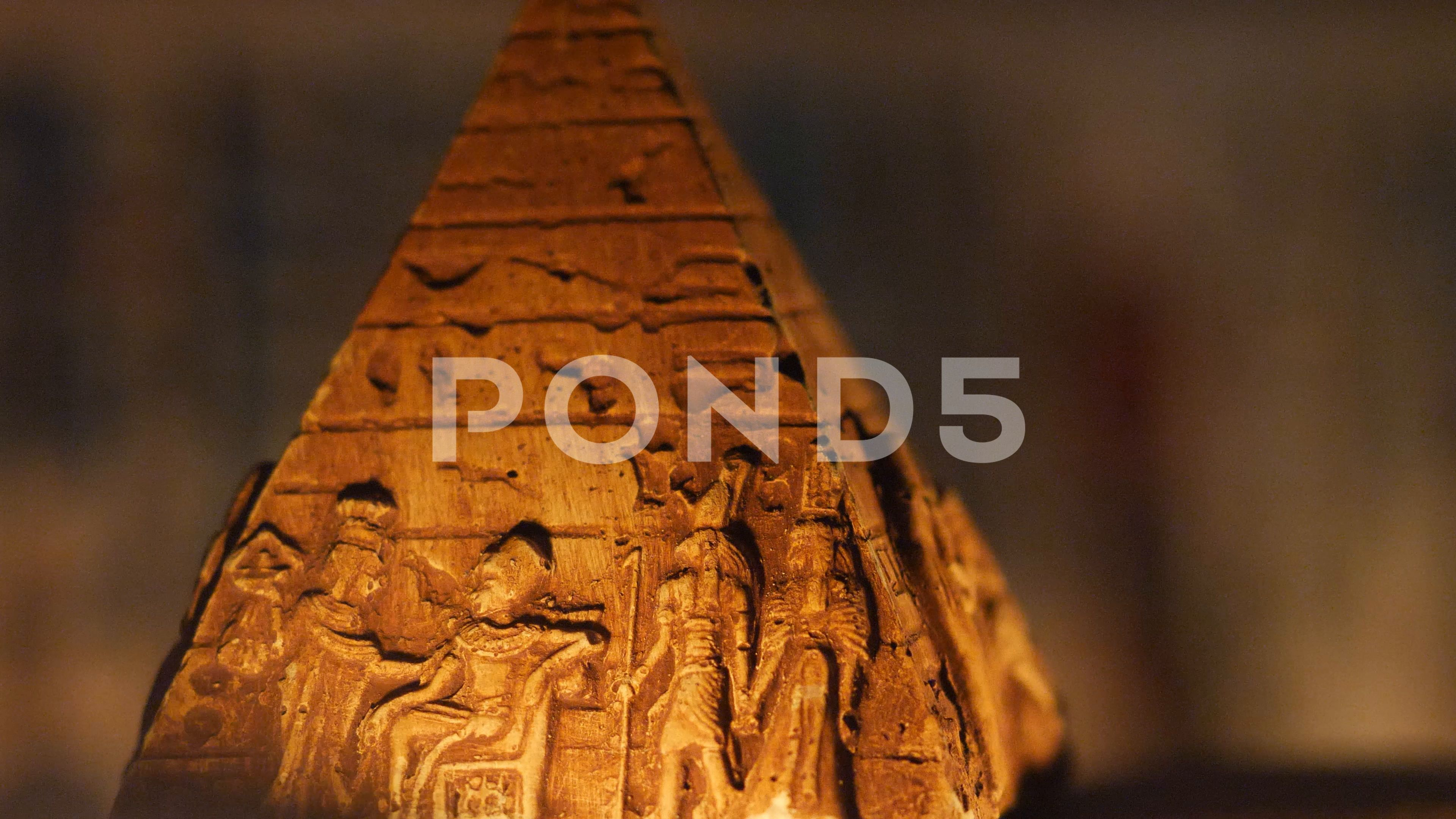 Old egyptian pyramid carved rock sculpture closeup lighted by fire